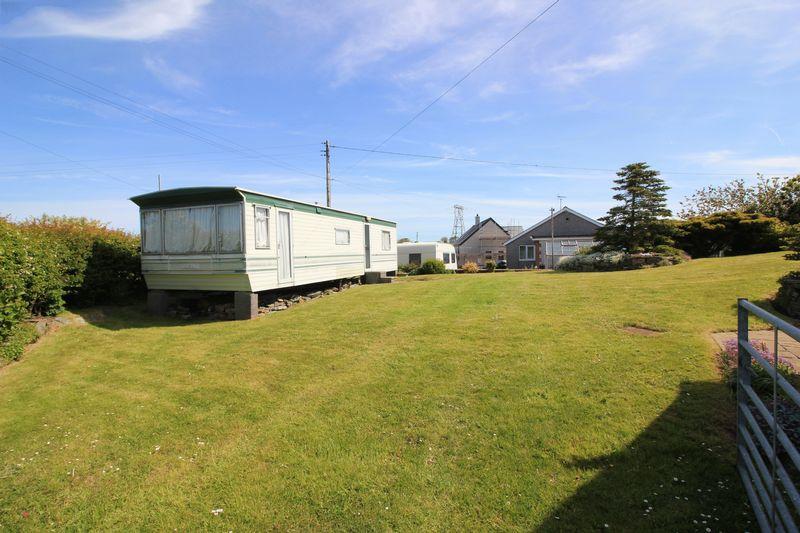 rear garden/grass parking and static caravan