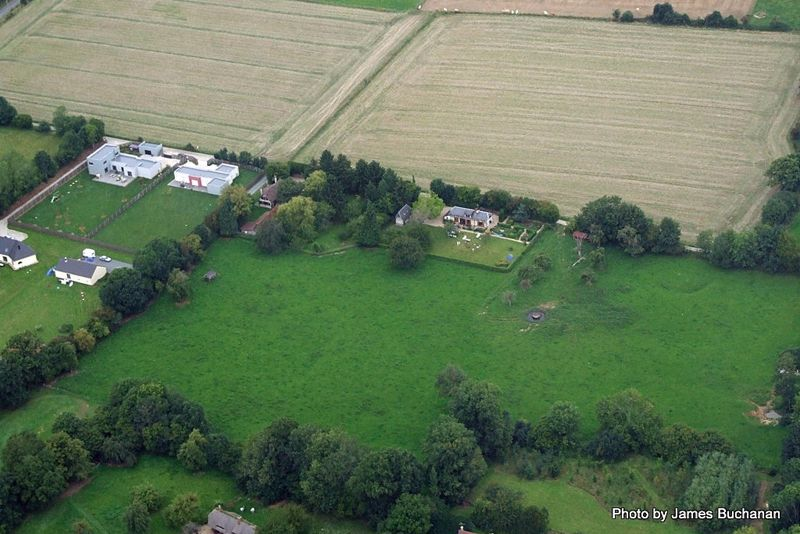A close aerial view of the house and field