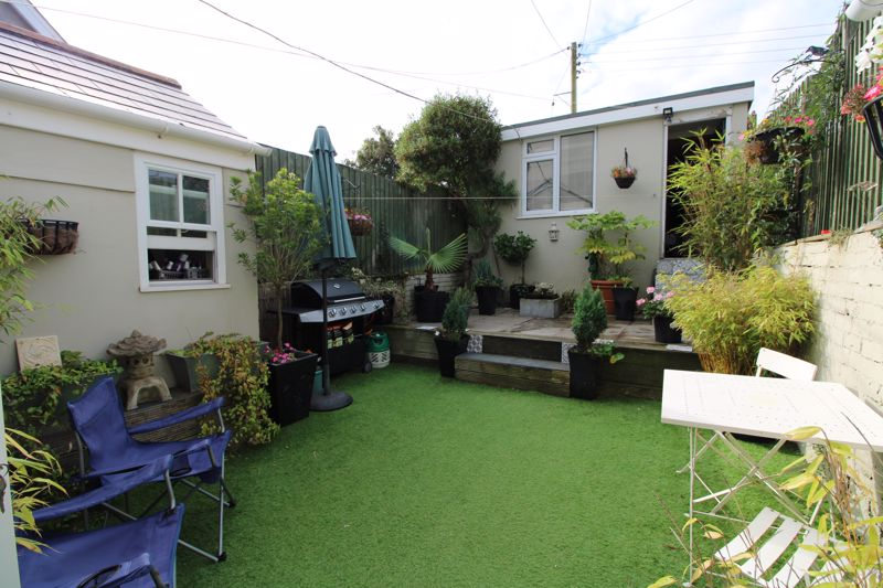 Enclosed low maintenance garden with workshop behi