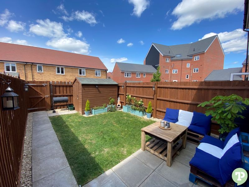 Landscaped rear garden with patio and garden shed